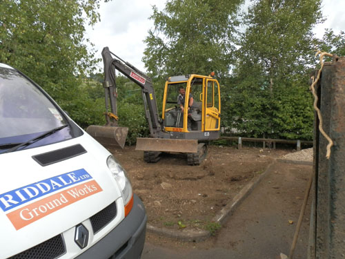 The digger sets to work clearing the rough ground